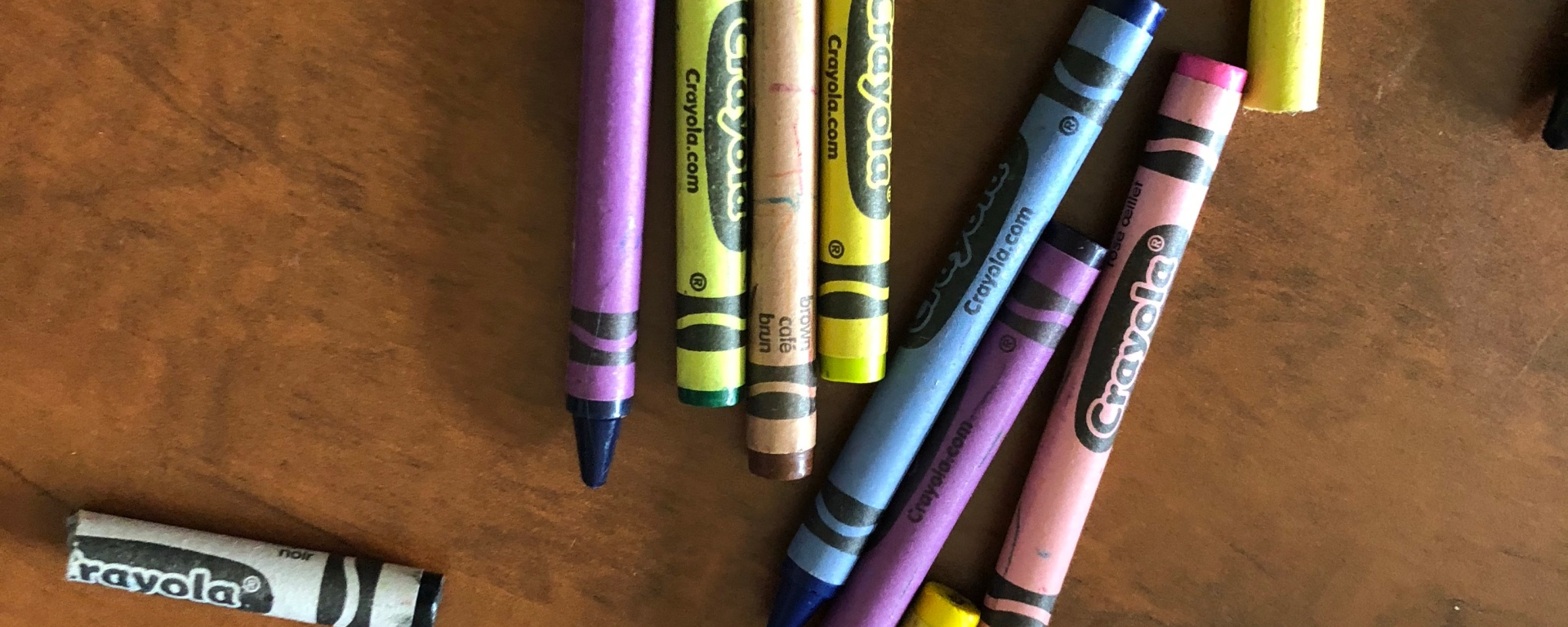 Crayons of various colors are sprawled across a brown table